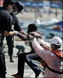 A migrant boy is helped off one of the boats in Tenerife
