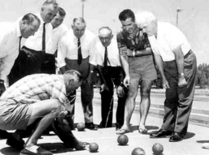 Old men in a huddle playing bocce