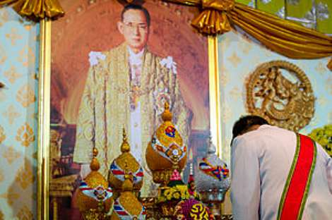 A government officer pays respect to the portrait of King Bhumibol Adulyadej of Thailand