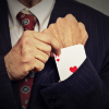 Man in suit pulls ace of hearts out of sleeve