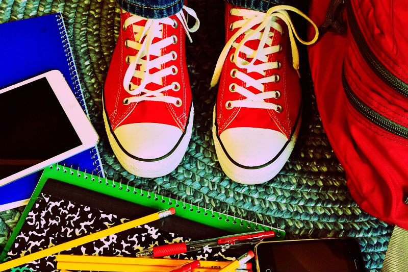 Books, pencils, tablet arrayed around a child's shoes