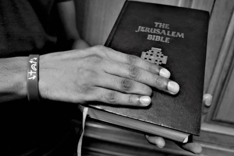 A Pakistani Christian asylum seeker, retrieves a copy of the Bible from a shelf at a Catholic organization's office in Bangkok. He lost part of a finger while working illegally in a workshop. (Photo by Tibor Krausz/ucanews.com)