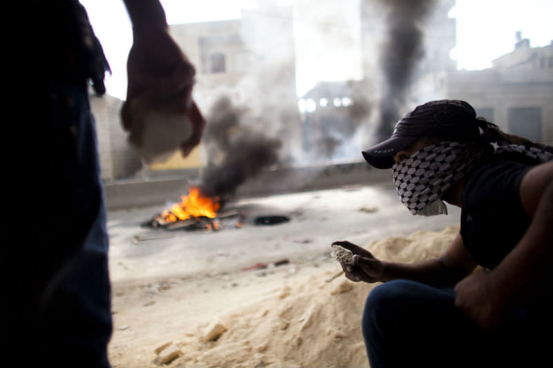 Palestinians burned tires and threw stones during clashes with the Israeli police on 15 May 15 2011 at Qalandiya checkpoint near Ramallah, West Bank. The day marked the 'Nakba' or 'catastrophe' which befell Palestinians following Israel's establishment in 1948. (Photo by Uriel Sinai/Getty Images)