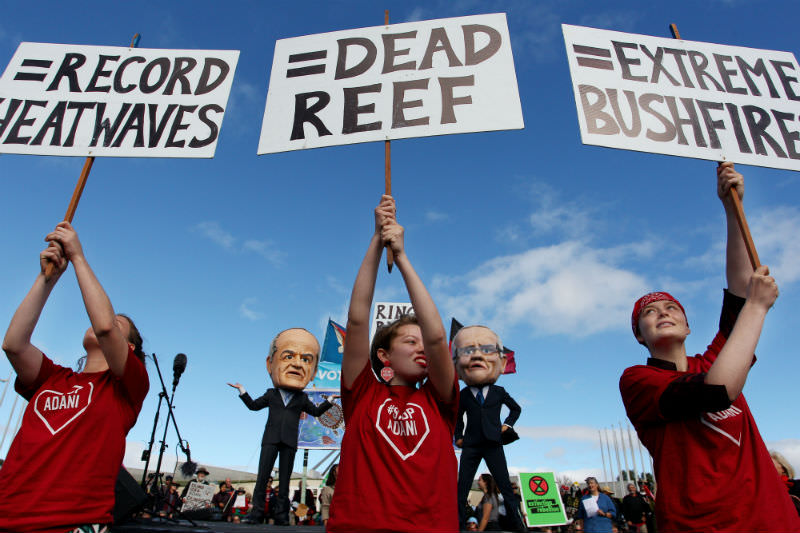 Young environment activists hold protest signs up in front of comedians dressed as Labor leader Bill Shorten and Prime Minister Scott Morrison as part of the anti-Adani convoy led by former Greens leader, Bob Brown. (Photo by Lisa Maree Williams/Getty Images)