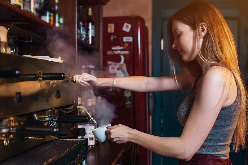 Woman barista working a coffee machine (Photo credit: undrey / Getty Creative)