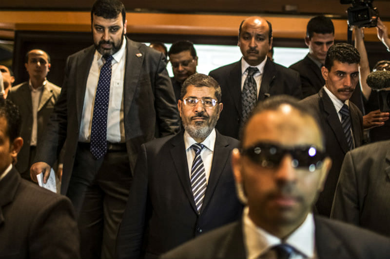Then presidential candidate Mohamed Morsi (centre) prior to speaking at a press conference in Cairo on 13 June 2012. (Photo by Daniel Berehulak/Getty Images)