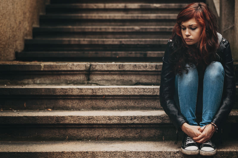 Forlorn looking woman in leather jacket sitting on steps. Stock photo by pixelfit via Getty