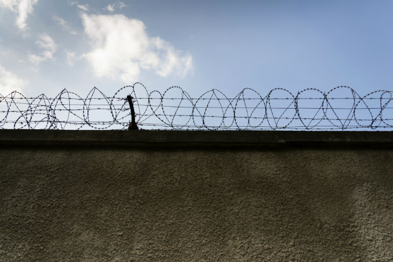 Prison wall barbed wire fence with blue sky background (Photo by josefkubes/Getty Images).