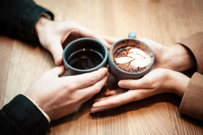 Two hands holding coffees on top of a table (Image: Jonathan J. Castellon/Unsplash)