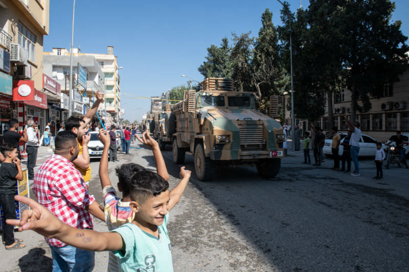 Turkish armoured vehicles escort members of the Turkish-backed Free Syrian Army, a militant group active in parts of northwest Syria, as they enter Syria on 10 October 2019. (Photo by Burak Kara/Getty Images)