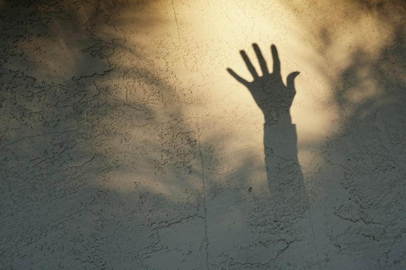 Silhouette of a reaching hand (Melinda Podor / Getty)