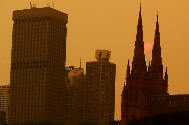 The sun sets behind St Mary's Cathedral in smoke-hazed Sydney on 6 December 2019 in Sydney, Australia. (Photo by Cameron Spencer/Getty Images)