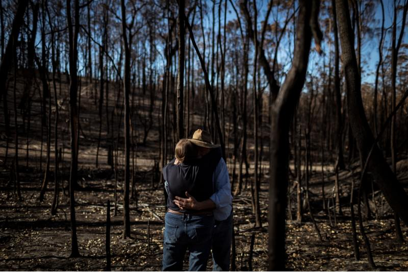 Elizabeth Blakeman embraces her husband Brian amongst the bushfire ravaged forest on their property on 12 January 2020 in Wairewa, Vic. (Photo by Chris Hopkins/Getty Images)