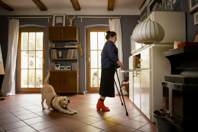 Woman in her home, using crutches. Her dog is stretching behind her. (Getty images/jacobia dahm)