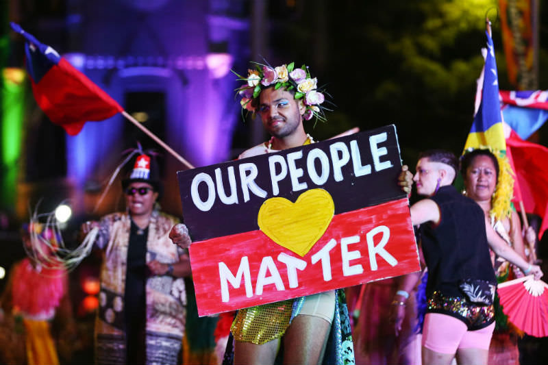 Sydney Mardi Gras 2020 person holds up sign with the colours of the Aboriginal flag reading, 'Our lives matter' (Getty Images/Brendon Thorne)