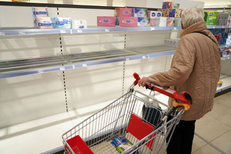 Elderly woman standing in front of cleared out shelves (Getty Images/Sean Gallup)