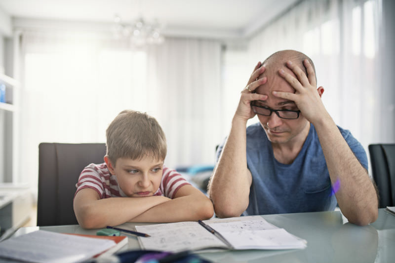 Parent and child struggling over homework (Getty)