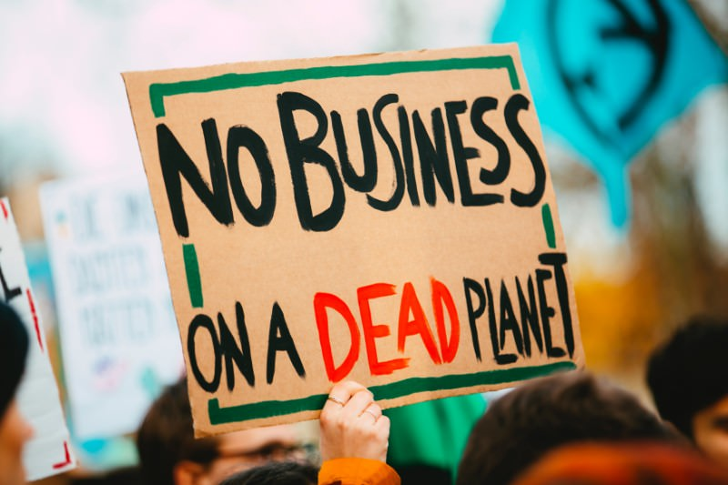 Sign reads No business on a dead planet (Markus Spiske/Unsplash)