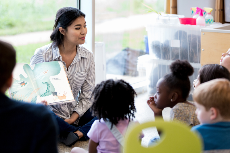 Woman reading picture storybook to young children  (SDI Productions/Getty Images)