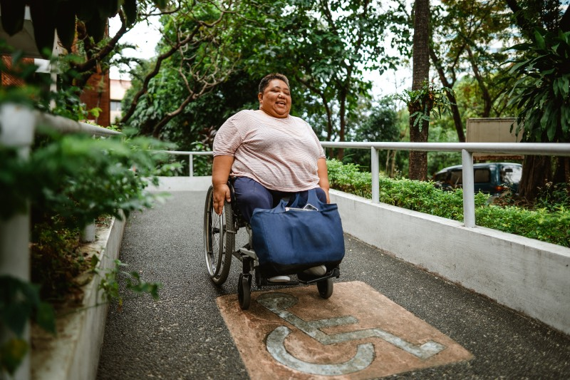 Woman using a wheelchair to go down a ramp (Iya Forbes/Getty Images)