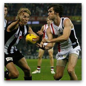 St Kilda's Farren Ray handballs under pressure from Collingwood's Dale Thomas