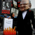 Protestor dressed as Rupert Murdoch burning Leveson report