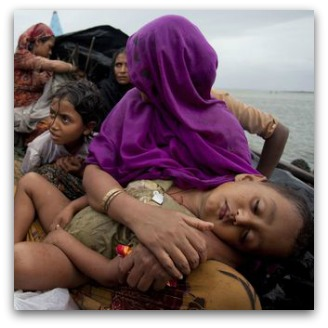 Rohingya asylum seekers on a boat, woman holds child
