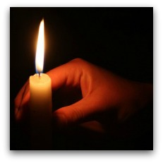 Hand holds candle in dark