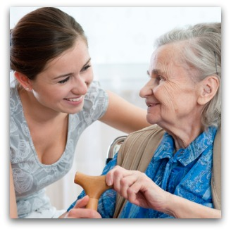 Carer and elderly woman smile at each other