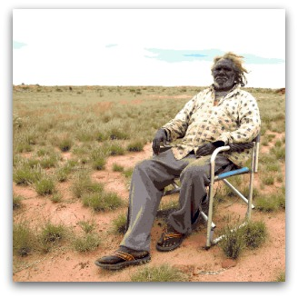Aboriginal man Tjungarryi sits in a camping chair against desert backdrop