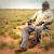 Aboriginal man Tjungarryi sits in camping chair against desert backdrop