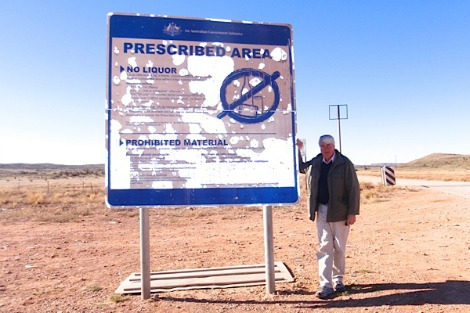 Frank Brennan on the road into Santa Teresa, Northern Territory. Old metal sign indicates that no alcohol is permitted ahead