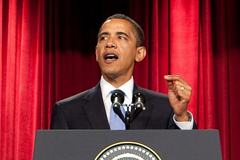 Barack Obama gesturing as he gives a speech in front of a red curtain