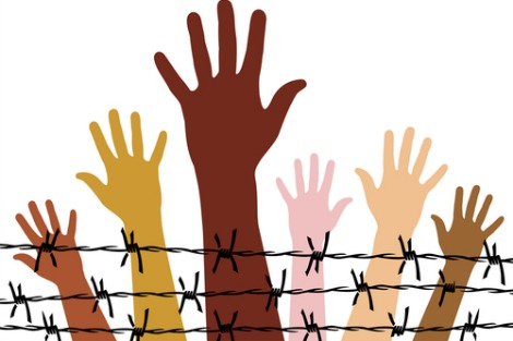 Diversely coloured hands behind barbed wire fence