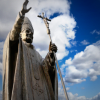 Statue of Pope John Paul II framed against blue sky