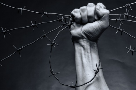 Fist clutching barbed wire