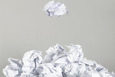 Crumpled ball of paper falls onto pile