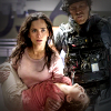 Woman played by Alice Braga carries a young unconscious girl watched over by a futuristic looking military man