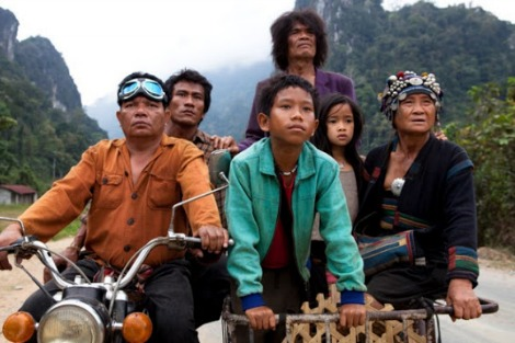 Scene from 'The Rocket'. Young Lao boy and girl, old lady and man in purple suit riding in a motorcycle side car through picturesque Laos mountains