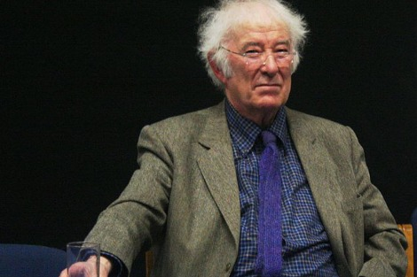 Seamus Heaney seated at a desk