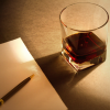 Glass of alcohol beside blank notepad