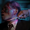 Anwar Congo in fake blood make-up with a knife to his throat