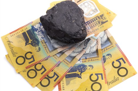 Lump of coal sitting on $50 notes