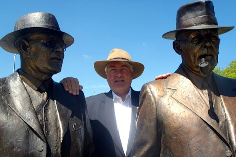 Frank Brennan stands between statues of Chifley and Curtin