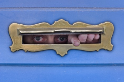 Man peeks through a mail slot