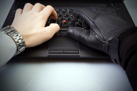 Black gloved hand on a computer keyboard