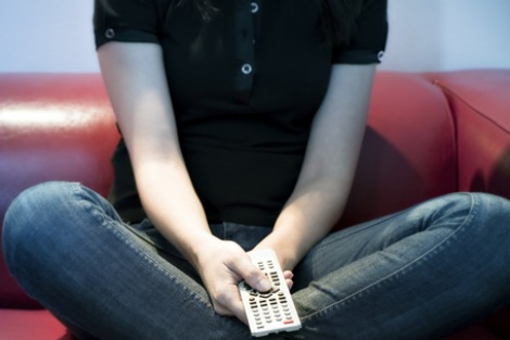 Person sitting cross legged on couch clutching remote control