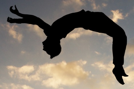 Gymnast performs a backflip, silhouetted against the sky