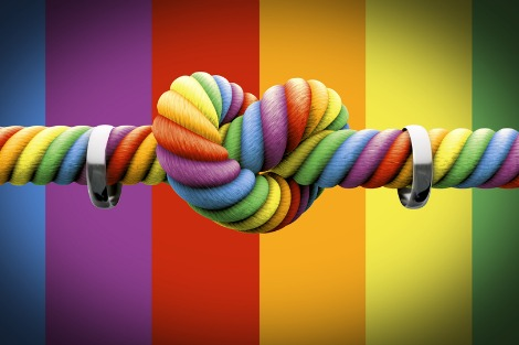 Rainbow coloured rope tied in a heart-shaped knot, with a wedding band strung on either side