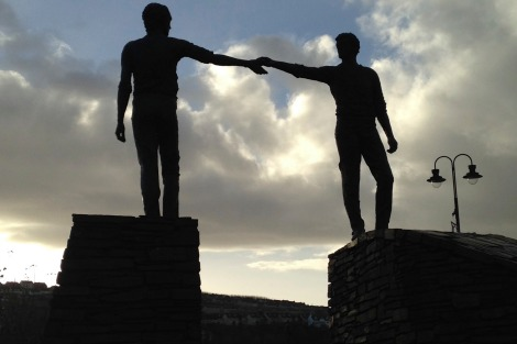 A sculpture at the city end of the main bridge that brings visitors into Derry portrays two figures reaching towards each other with outstretched arms